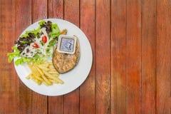 Filete de color salmón asado a la parrilla, servicio con las patatas fritas y vegetabl de la ensalada Imagen de archivo libre de regalías