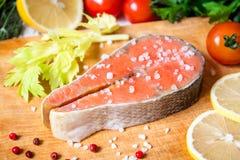 Filete de color salmón crudo fresco en tabla de cortar con la sal y la pimienta rosada Foto de archivo