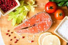 Filete de color salmón crudo fresco en tabla de cortar con la sal y la pimienta rosada Fotos de archivo