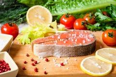 Filete de color salmón crudo fresco en tabla de cortar con la sal y la pimienta rosada Imagen de archivo libre de regalías