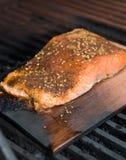 Filete de color salmón en el humo del tablón del cedro que cocina en el Bbq Imágenes de archivo libres de regalías