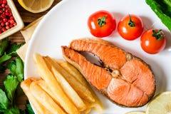 Filete de color salmón frito con las verduras en la placa Foto de archivo