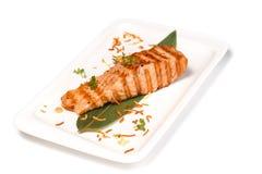 Filete de pescados rojo asado a la parrilla en una hoja de bamb? en una placa rectangular en un fondo blanco aislado fotos de archivo