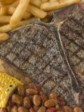 Filete de T-Bone con las fritadas maíz y habas Fotografía de archivo