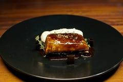Filete del cerdo en un plato negro Imagenes de archivo