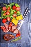 Filete del cordero del Bbq con la ensalada y el maíz vegetales en la parte posterior de madera oscura Fotografía de archivo libre de regalías