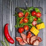 Filete del cordero del Bbq con la ensalada y el maíz vegetales en la parte posterior de madera oscura Foto de archivo libre de regalías