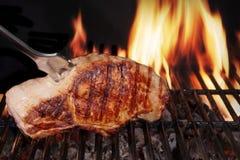 Filete del lomo de cerdo en parrilla llameante caliente de la barbacoa con la bifurcación Imagenes de archivo