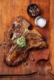 Filete del T-hueso y mantequilla de hierba asados a la parrilla Foto de archivo libre de regalías