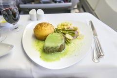 Filete determinado de la comida de aviones en una bandeja, en una tabla blanca Fotos de archivo
