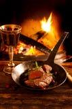 Filete en cacerola con el fuego de la chimenea Foto de archivo libre de regalías