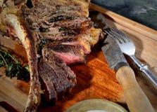 Filete frito con las especias, el cuchillo del vintage y la bifurcación aromáticos en un fondo de madera Fotografía de archivo