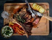 Filete frito con las especias, las salmueras, la salsa, el cuchillo y la bifurcación aromáticos en un fondo de madera, visión sup Imagen de archivo libre de regalías