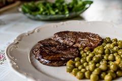 Filete hecho en casa del filete con los guisantes y la ensalada verde en la tabla de cocina imagen de archivo