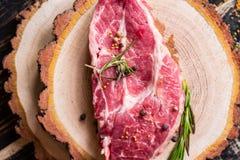 Filete jugoso crudo de la carne en el fondo de madera oscuro listo a la asación Foto de archivo libre de regalías