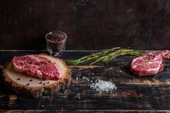 Filete jugoso crudo de la carne en el fondo de madera oscuro listo a la asación Imagen de archivo