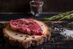 Filete jugoso crudo de la carne en el fondo de madera oscuro listo a la asación Imágenes de archivo libres de regalías