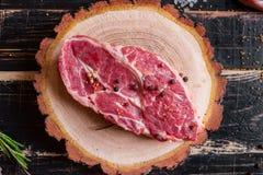 Filete jugoso crudo de la carne en el fondo de madera oscuro listo a la asación Imagen de archivo libre de regalías