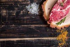 Filete jugoso crudo de la carne en el fondo de madera oscuro listo a la asación Fotos de archivo