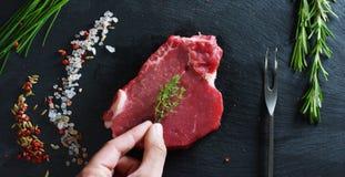Filete jugoso hermoso de la carne fresca en una tabla con la sal, el romero, el ajo, y el tomate en un fondo negro, visión superi Fotos de archivo