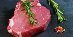 Filete jugoso hermoso de la carne fresca en una tabla con la sal, el romero, el ajo, y el tomate en un fondo negro, visión superi Imagen de archivo