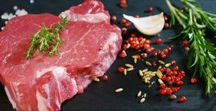 Filete jugoso hermoso de la carne fresca en una tabla con la sal, el romero, el ajo, y el tomate en un fondo negro, visión superi Fotografía de archivo