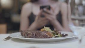 Filete sabroso con las verduras y las hojas que mienten en la placa delante de la mujer en el restaurante El mandar un SMS de las almacen de metraje de vídeo