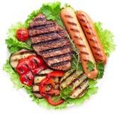 Filete, salchichas y verduras asados a la parrilla. imagen de archivo libre de regalías