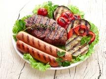 Filete, salchichas y verduras asados a la parrilla. imágenes de archivo libres de regalías