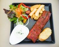 Filete y ensalada de carne de vaca en plato negro Foto de archivo