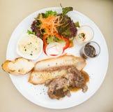 Filete y ensalada en el plato blanco Imagen de archivo libre de regalías