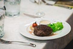 Filete y salsa asados a la parrilla frescos de rosbif del Bbq en una placa blanca con la hoja verde de la ensalada salsa de la so Imágenes de archivo libres de regalías