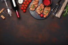 Filetes asados a la parrilla del cerdo en piedra con la botella de vino, de copa de vino, de cuchillo y de bifurcación en fondo o foto de archivo libre de regalías
