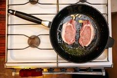 Filetes crudos de la carne de cerdo con las especias en un sartén, cocinando la cocina de la comida en casa Imagen de archivo libre de regalías