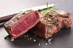 Filetes de carne de vaca en pizarra negra Foto de archivo libre de regalías