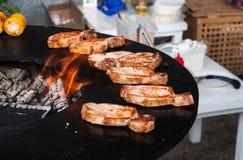 Filetes de carne de vaca deliciosos en la parrilla con las llamas Imagen de archivo