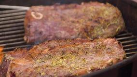 Filetes de carne de vaca en la parrilla con las llamas Cocinar los filetes en los carbones Concepto de comer la carne almacen de metraje de vídeo