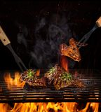 Filetes de carne de vaca en la parrilla con las llamas imagen de archivo libre de regalías