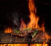 Filetes de carne de vaca en la parrilla con las llamas imagen de archivo