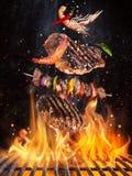 Filetes de carne de vaca sabrosos y pinchos que vuelan sobre la rejilla del arrabio con las llamas del fuego imagen de archivo libre de regalías