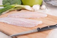 Filetes de pescados descongelados con las verduras Fotos de archivo libres de regalías