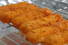 Filetes de pescados empanados en una parrilla Foto de archivo libre de regalías
