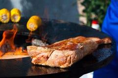 Filetes y maíz deliciosos de carne de vaca en la parrilla con las llamas Fotos de archivo