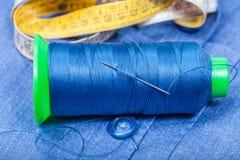 Filetez la bobine, le bouton, bande de mesure sur le tissu bleu Photographie stock libre de droits