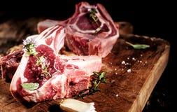 Filets chevronnés crus d'agneau sur le conseil en bois rustique images libres de droits