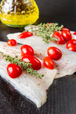 Filets crus de bar de mer avec des tomates-cerises sur le bois noir Photographie stock libre de droits