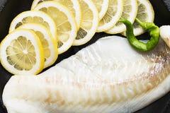 Filets de morue crus avec des tranches de citron sur un plateau noir de cuisson Vue supérieure Images libres de droits
