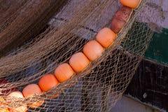 Filets de pêche avec les flotteurs lumineux Grands flotteurs de rouge Filets de pêche de séchage dans le port maritime Images stock