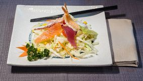 Filets de poisson cru mélangés sur la salade, cousine de fusion Photo libre de droits