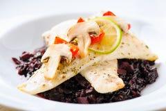 Filetti di merluzzo sopra riso nero Fotografie Stock